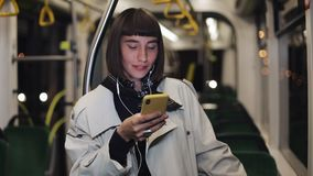 O retrato da jovem mulher bonita nos fones de ouvido que montam em público o transporte, escuta música e consultando no amarelo video estoque