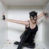 O retrato da jovem mulher da beleza na máscara gosta do gato na caixa branca Fotografia de Stock