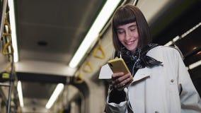 O retrato da jovem mulher de sorriso nos fones de ouvido que montam em público o transporte, escuta música e consultando no smart video estoque