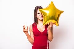 O retrato da jovem mulher no vestido vermelho com estrela do ouro deu forma ao champanhe de sorriso e bebendo do balão Fotos de Stock