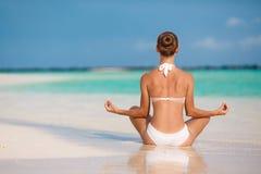 O retrato da jovem mulher que faz a ioga exercita na praia maldiva tropical perto do oceano imagens de stock royalty free