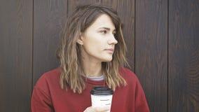 O retrato da jovem mulher que veste uma camiseta vermelha está bebendo o café Imagem de Stock