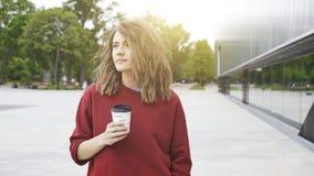 O retrato da jovem mulher que veste uma camiseta vermelha está bebendo o café para ir ao estar perto de uma parede de madeira Tir Imagem de Stock