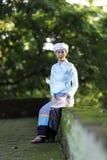O retrato da jovem mulher tailandesa com o vestido tailandês tradicional senta-se no templo tailandês com árvore e nascer do sol imagens de stock