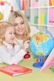 O retrato da mãe com filha pequena examina o globo imagem de stock
