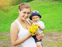 O retrato da mãe e do bebê felizes com dente-de-leão amarelo floresce Imagens de Stock Royalty Free