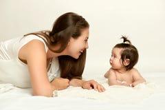 O retrato da mãe e do bebê que têm o divertimento, mentira no branco, amarela tonificado imagem de stock