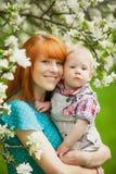 O retrato da mãe feliz feliz e o filho na mola jardinam foto de stock