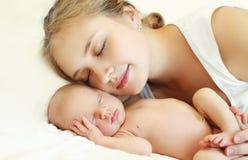 O retrato da mãe e o bebê dormem junto na cama Foto de Stock