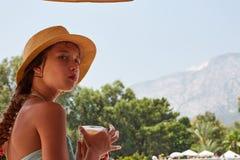 O retrato da menina é suco fresco do drainkig, terras da montanha do verão imagens de stock royalty free