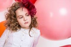 O retrato da menina adolescente em um chapéu e o branco vestem-se em um fundo o Fotografia de Stock