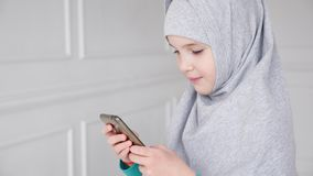 O retrato da menina adolescente muçulmana nova no hijab cinzento está jogando o smartphone filme