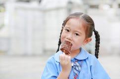 O retrato da menina asiática pequena da criança na farda da escola aprecia comer o gelado saboroso de baunilha do chocolate imagens de stock royalty free