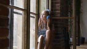 O retrato da menina atrativa nova no fundo da janela está escutando a música com fones de ouvido Uma menina adolescente bonita se video estoque