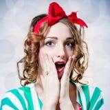 O retrato da menina bonita do pinup com olhos azuis surpreendeu a vista da câmera na luz - fundo azul do espaço da cópia Imagem de Stock Royalty Free