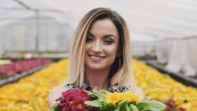 O retrato da menina bonita feliz mostra o vaso de flores na câmera com sorriso video estoque