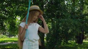 O retrato da menina bonita levanta na câmera com os balões coloridos no parque ensolarado vídeos de arquivo