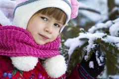 O retrato da menina bonita no inverno veste-se perto da tampa de neve Fotografia de Stock