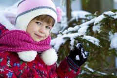 O retrato da menina bonita no inverno veste-se perto da tampa de neve Foto de Stock Royalty Free