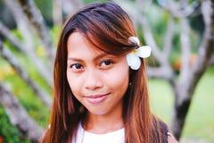 O retrato da menina bonita nova com o frangipani, plumeria floresce em seu cabelo Fotografia de Stock Royalty Free