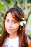 O retrato da menina bonita nova com o frangipani, plumeria floresce em seu cabelo Imagens de Stock
