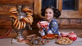 O retrato da menina bonita pequena vestida no traje tradicional senta-se na tabela na casa de madeira rural velha russian filme