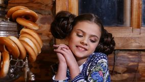 O retrato da menina bonita pequena vestida no traje tradicional senta-se na tabela na casa de madeira rural velha russian vídeos de arquivo