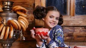 O retrato da menina bonita pequena vestida no traje tradicional senta-se na tabela na casa de madeira rural velha russian video estoque