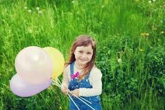 O retrato da menina bonito com o sorriso bonito que guarda o brinquedo balloons à disposição no prado da flor, infância feliz Imagem de Stock Royalty Free