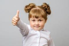 O retrato da menina bonito que mostra os polegares levanta o sinal fotografia de stock