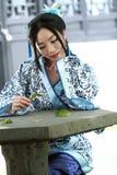 O retrato da menina chinesa asiática no vestido tradicional, veste azul e o estilo branco Hanfu da porcelana, senta-se em uma cad Foto de Stock