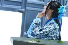 O retrato da menina chinesa asiática no vestido tradicional, veste azul e o estilo branco Hanfu da porcelana, senta-se em uma cad Imagens de Stock Royalty Free