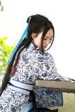 O retrato da menina chinesa asiática no vestido tradicional, veste azul e o estilo branco Hanfu da porcelana, senta-se em uma cad Fotografia de Stock Royalty Free