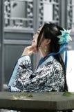 O retrato da menina chinesa asiática no vestido tradicional, veste azul e o estilo branco Hanfu da porcelana, senta-se em uma cad Fotos de Stock