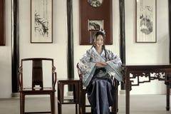 O retrato da menina chinesa asiática no vestido tradicional, veste o estilo azul e branco Hanfu da porcelana, sentar-se elegante  imagens de stock royalty free