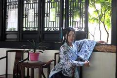 O retrato da menina chinesa asiática no vestido tradicional, veste o estilo azul e branco Hanfu da porcelana, sentar-se elegante  foto de stock