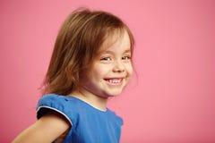 O retrato da menina da criança lateralmente, expressa o bom humor, sorrisos sinceros imagem de stock