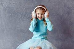 O retrato da menina de riso bonita em uma saia azul e a pele dirigem Fotografia de Stock