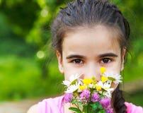 O retrato da menina de sorriso pequena com mola floresce o ramalhete Fotografia de Stock