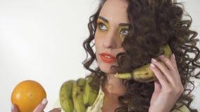 O retrato da menina encaracolado nova com brilhante compõe a vista na laranja com o interesse que imita uma conversação telefônic vídeos de arquivo