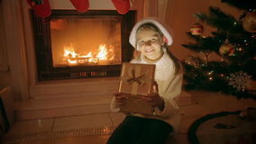 O retrato da menina entusiasmado feliz que senta-se na chaminé abre a caixa de presente do Natal video estoque