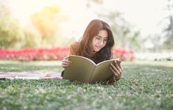 O retrato da menina da High School estabelece e lê um livro no parque foto de stock