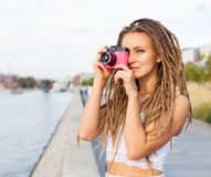 O retrato da menina na moda com teme e da câmera do vintage que está pelo rio Conceito moderno do estilo de vida da juventude Tom Imagens de Stock