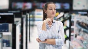 O retrato da menina nos cosméticos compra pensa que produto a comprar, movimento lento