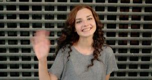 O retrato da moça vestiu-se na camisa cinzenta perto da cerca metálica oxidada A menina que sorri, diz olá! e renunciando à mão 4 filme