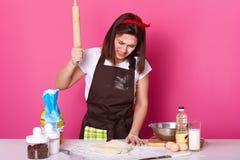 O retrato da morena nova forçou o funcionamento fêmea no dia inteiro da cozinha, preparando a pastelaria caseiro, parece cansado  foto de stock royalty free
