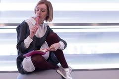 O retrato da mulher à moda moderna escreve no bloco de notas Fotografia de Stock Royalty Free