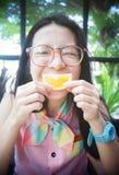 O retrato da mulher asiática feliz em um café com laranja do mandlin contra de uma boca como um sorriso, diz o conceito do queijo Fotos de Stock Royalty Free