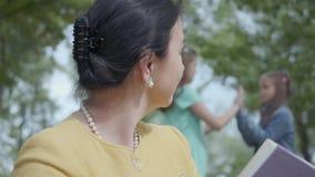 O retrato da mulher bonita madura que l? um livro e suas netas jogam junto no parque no fundo filme