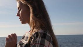 O retrato da mulher bonita na praia pelo vento do oceano funde vídeos de arquivo